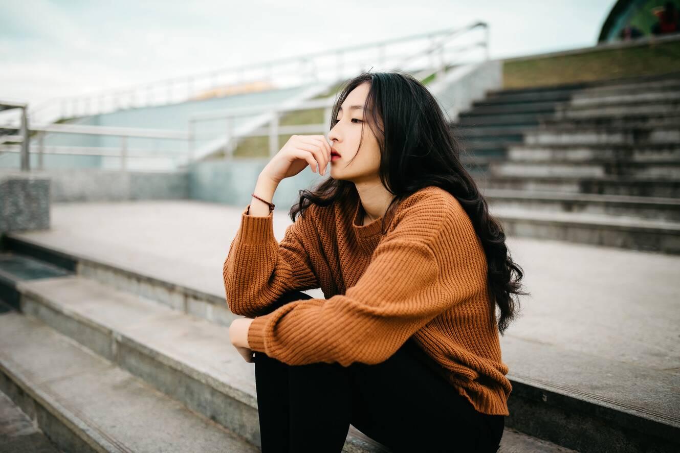 young asian teenage girl wearing dark orange sweater sitting on concrete steps