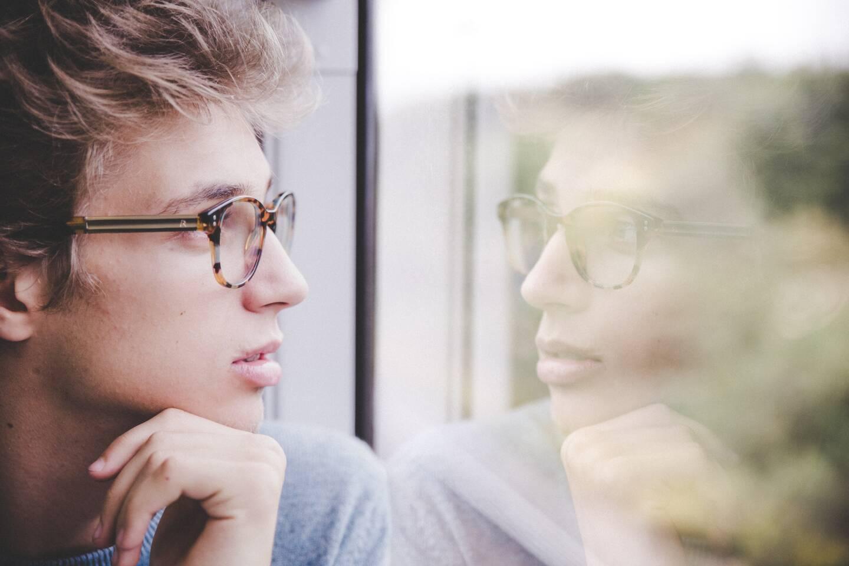 teenage boy looking out of train window